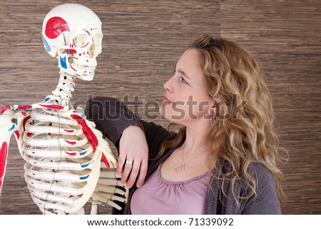 A portrait of a woman and a skeleton. - stock photo