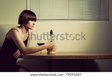 A portrait of a woman drinking wine alone by candlelight. - stock photo