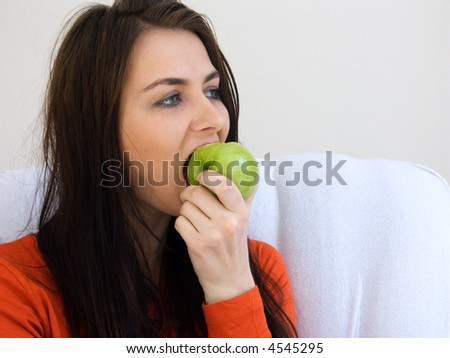 A portrait of a woman eating a green apple. - stock photo