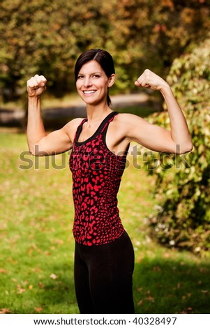 A portrait of a woman flexing her bicep muscles - stock photo