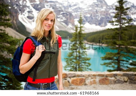 A portrait of a woman hiking on a mountain path near a lake - stock photo