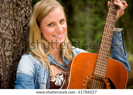 A portrait of a woman holding a guitar in an outdoor setting