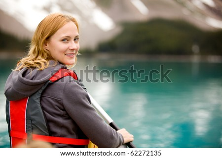 A portrait of a woman on a lake in a canoe - stock photo