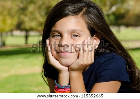 a portrait of a 10 year old boy who is smiling int he park. - stock photo