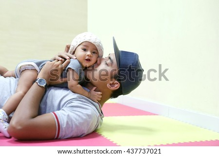 A portrait of a Young Asian father holding and kissing his adorable baby - stock photo