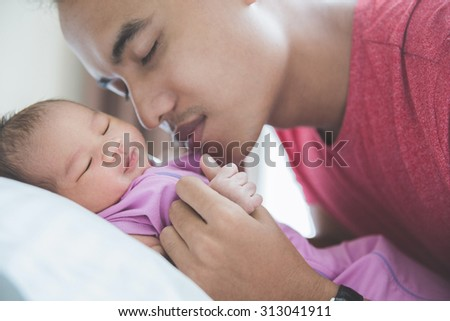 A portrait of a young Asian father kissing his newborn sleeping baby, close eyes - stock photo