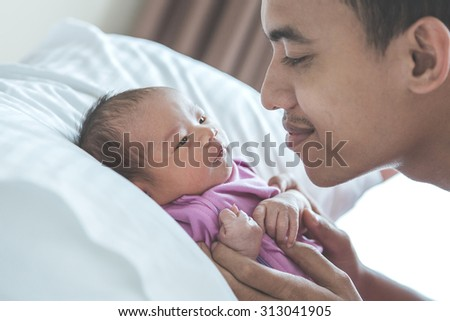 A portrait of a young Asian father looking at his newborn baby, close up