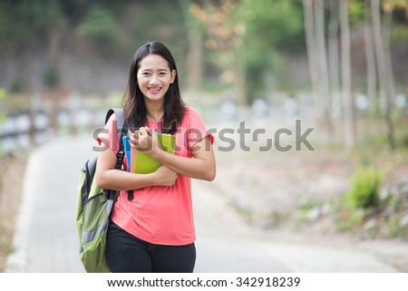 A portrait of a young Asian students outdoor, posing cutely to the camera