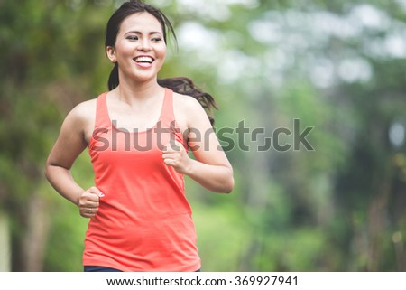 A portrait of a young asian woman doing exercise outdoor in a park, jogging - stock photo