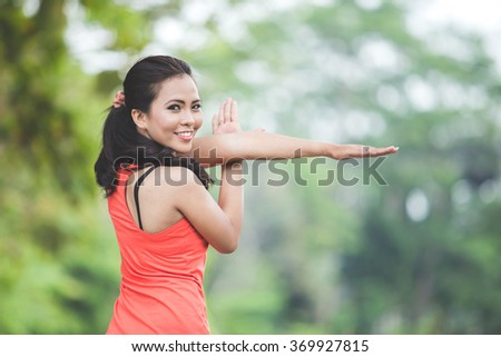A portrait of a young asian woman doing exercise outdoor in a park, stretching