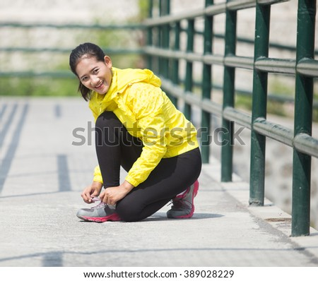 A portrait of a young asian woman exercising outdoor in yellow neon jacket, tying her shoelace - stock photo