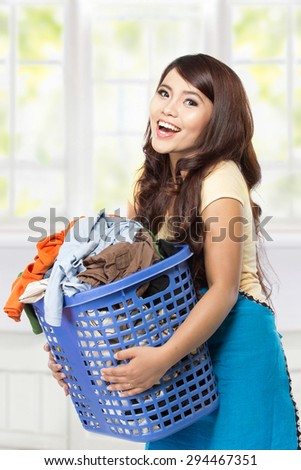 A portrait of a young asian woman holding a basket full of clothes
