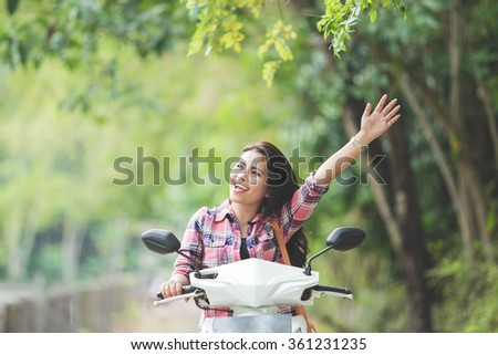 A portrait of a young asian woman riding a motorcycle on a park, hand up - stock photo