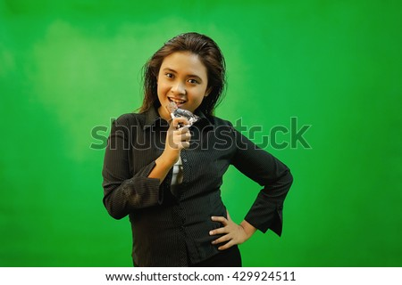 A portrait of a young asian woman smiling and gestures while standing - green screen for compositing