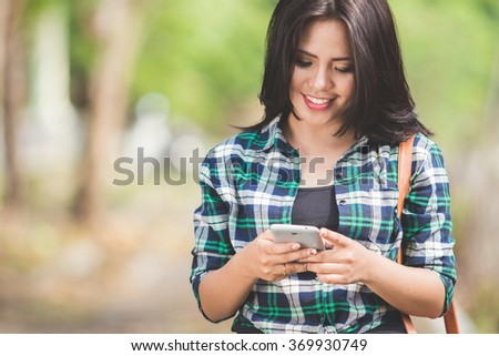 A portrait of a young asian woman using a cellphone while walking on the park - stock photo