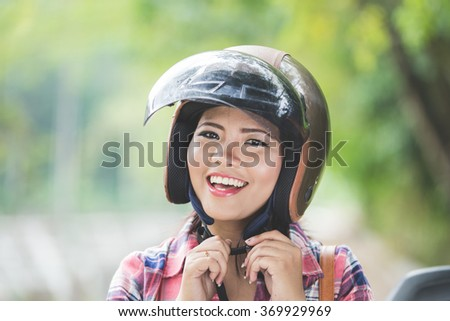 A portrait of a young asian woman wearing a helmet before riding a motorcycle on a park - stock photo
