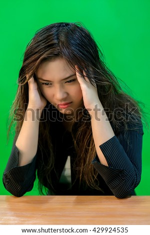 A portrait of a young asian woman with tired and under-pressure expression while sitting - green screen for compositing