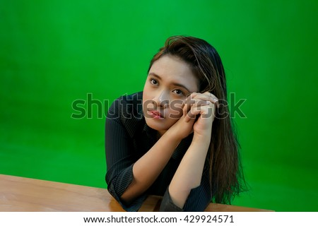 A portrait of a young asian woman with tired expression while sitting - green screen for compositing - stock photo