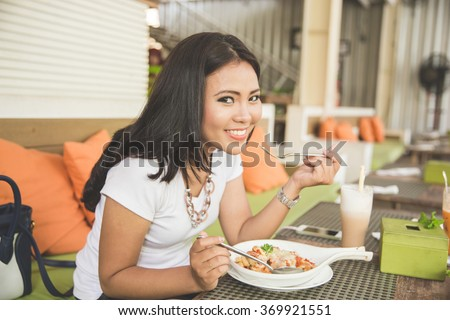 A portrait of a young beautiful asian woman in a restaurant, enjoying her food