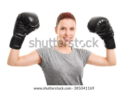 A portrait of a young beautiful girl with boxing gloves cheering, isolated on white background. - stock photo