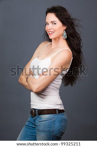 A portrait of a young beautiful woman wearing jeans and singlet - stock photo