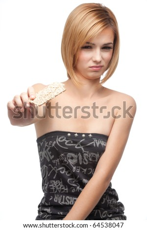 a portrait of a young, blonde woman, holding in one of her hands a slice of bio bread from which she just had a taste, showing it to the camera, and having a disgusted and sad expression on her face. - stock photo