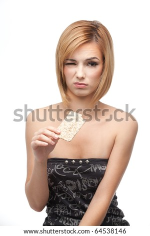 a portrait of a young, blonde woman, holding in one of her hands a slice of bio bread from wich she just had a taste, having a disgusted and sad expresion on her face. - stock photo