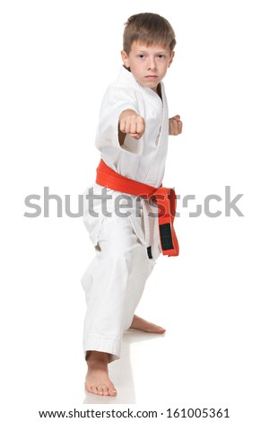 A portrait of a young boy in kimono in fighting stance