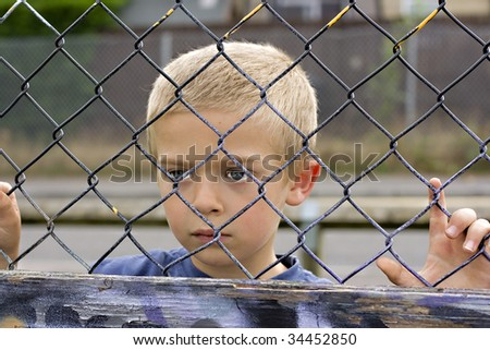 A portrait of a young boy looking through a chain link fence - stock photo