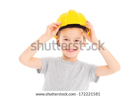 A portrait of a young boy trying on a yellow hard hat over white background - stock photo