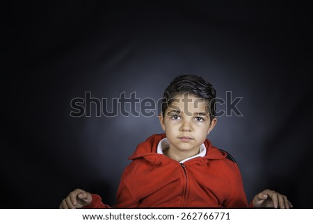 A portrait of a young boy wearing a red hoodie against a black background - stock photo