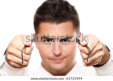 A portrait of a young businessman holding glasses, focus on eyes and glasses