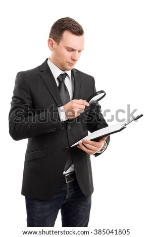 A portrait of a young businessman looking at the clipboard through a magnifying glass, isolated on white background. - stock photo