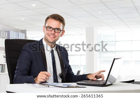 A portrait of a young businessman posing in front of laptop