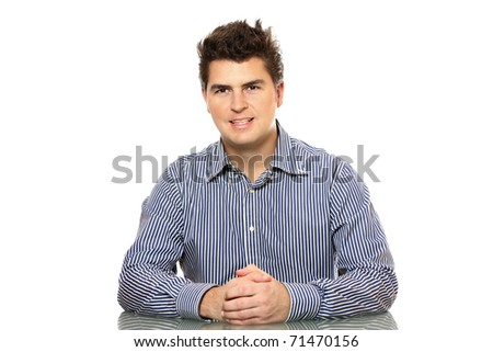 A portrait of a young businessman sitting behind the desk in the office - stock photo