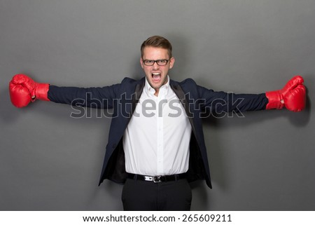 A portrait of a young businessman with boxing gloves, scream - stock photo