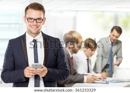 A portrait of a young caucasian businessman, with his team behind holding cellphone