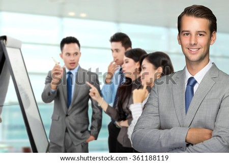 A portrait of a young caucasian businessman, with his team discussing at the background - stock photo