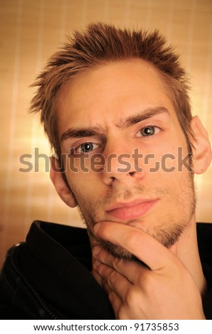 A portrait of a young Caucasian male in his early 20s thinking while scratching his chin - stock photo