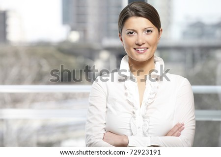A portrait of a young confident woman standing against light background - stock photo
