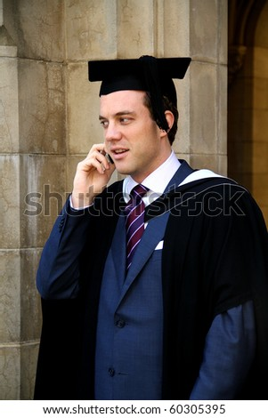 A portrait of a young European man in a graduation gown and taking on the phone. - stock photo
