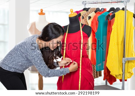 A portrait of a young fashion designer or Tailor working on a design or draft, she make a little adjustment to her work - stock photo