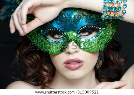 A portrait of a young female masked in a studio. - stock photo