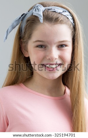 A portrait of a young girl with a grey background. She is looking at the camera and smiling. - stock photo