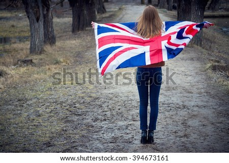 A portrait of a young girl with flag of United Kingdom on her back in summertime. - stock photo