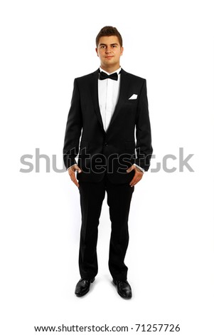 A portrait of a young groom in a tuxedo standing over white background