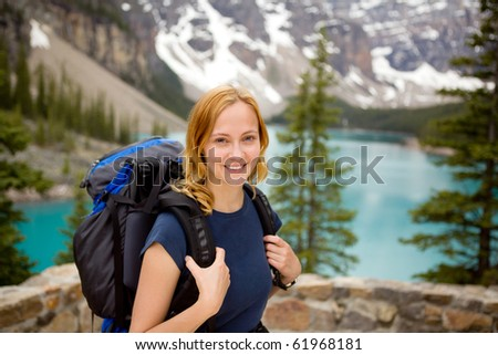 A portrait of a young happy woman infront of a beautiful mountain landscape