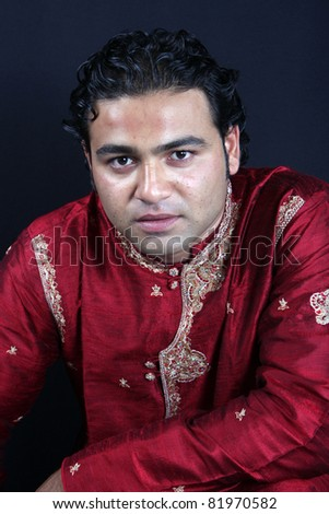 A portrait of a young Indian man in a traditional attire. - stock photo