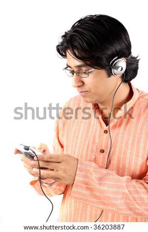 A portrait of a young Indian teenager in a traditional attire, listening to a MP3 Player. - stock photo