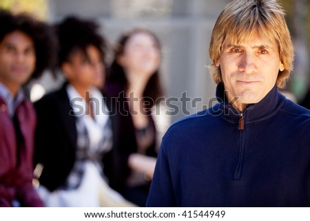 A portrait of a young man and a group of friends - stock photo